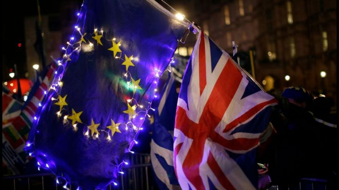 Standing outside the Houses of Parliament in London on Wednesday, a person holds a EU and British union flag, signifying their support for the UK to remain in the European Union.