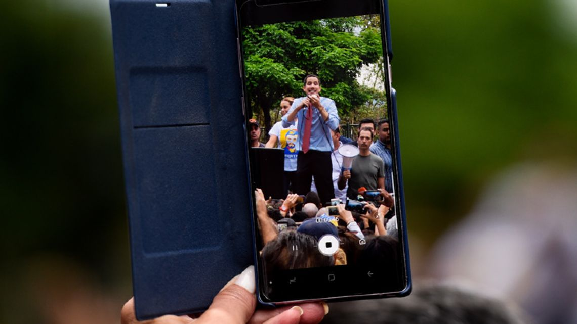 A woman films with her mobile phone as Venezuelan opposition leader and self-proclaimed acting president Juan Guaidó speaks during a protest in the fifth day of a crippling power blackout, in Caracas on March 12, 2019.