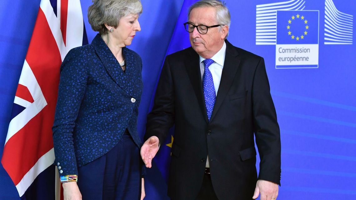 In this Thursday, Feb. 7, 2019 file photo European Commission President Jean-Claude Juncker prepares to shake hands with British Prime Minister Theresa May before their meeting at the European Commission headquarters in Brussels