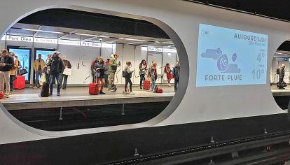 Estaciones tecnológicas. En Lyon, Francia, pasajeros esperan el subte. Hay data del clima y más info proyectada en el andén.