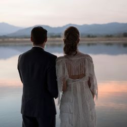 Bride Maria Fernanda Vera and groom Juan Jose Pocaterra pose for a photo at a lake after their marriage ceremony as the sun sets in Acarigua, Venezuela