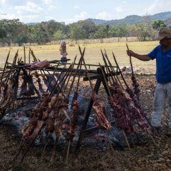 A man roasts meat for a destination wedding party. In the grassy fields, workers sacrificed a cow and a pig to grill them on a stake, and set up a stage for the party worthy of a rock concert.