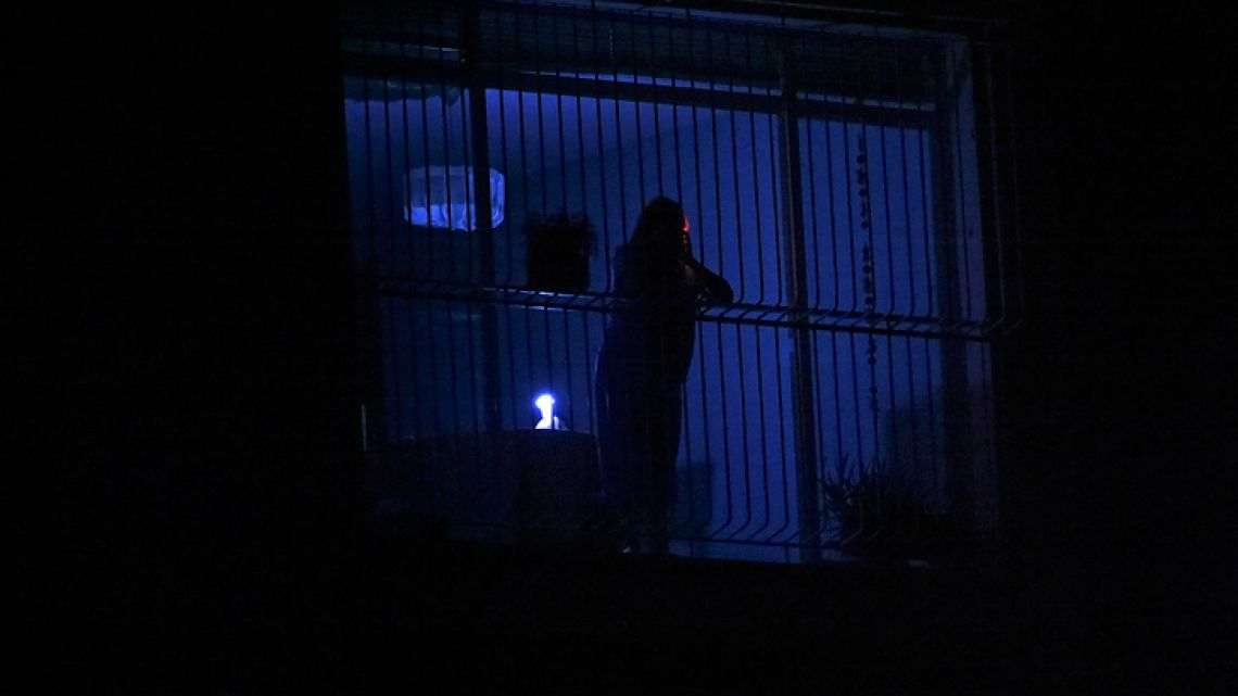 A person looks through the window during a power outage in Caracas on March 25 , 2019. A new blackout hit many regions in Venezuela including much of Caracas on March 25, sowing alarm two weeks after a nationwide outage that paralyzed the country. The power cut in the capital occurred at 1:28 pm (1720 GMT) and knocked out electricity in the city center. Cellphone signals were also disrupted and television was blanked out. Shops hastily lowered shutters, fearing looters. A Venezuelan newspaper reported that the power was out at Venezuela's main international airport outside Caracas.
