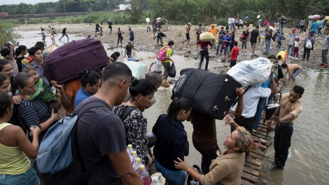 People cross from the Colombian border back to Venezuela after buying goods to resell, through an improvised bridge on an illegal trail. Venezuela is in the grip of a humanitarian crisis due to shortages of food and medicine exacerbated by hyperinflation.