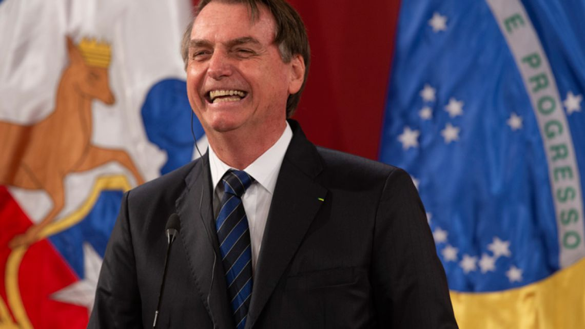 Brazil's President Jair Bolsonaro laughs during a joint press conference with Chilean President Sebastian Piñera (out of frame) at the La Moneda Presidential Palace in Santiago, on March 23, 2019.