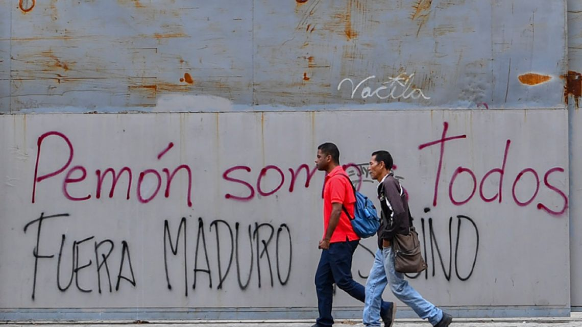 Pedestrians walk by anti-Maduro graffiti during a power outage in Caracas on March 26, 2019. A new blackout swept across Venezuela on Monday, including much of Caracas, sowing alarm two weeks after a nationwide outage that paralyzed the country.
