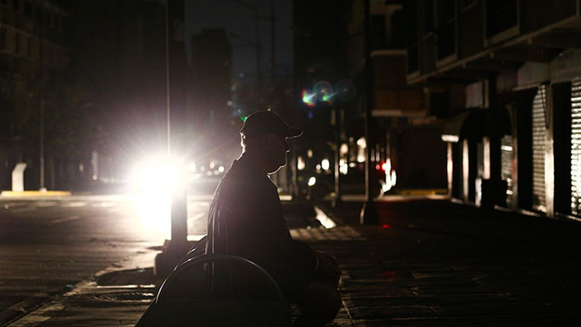A man sits on a bench in pitch dark, during a power cut in Caracas.