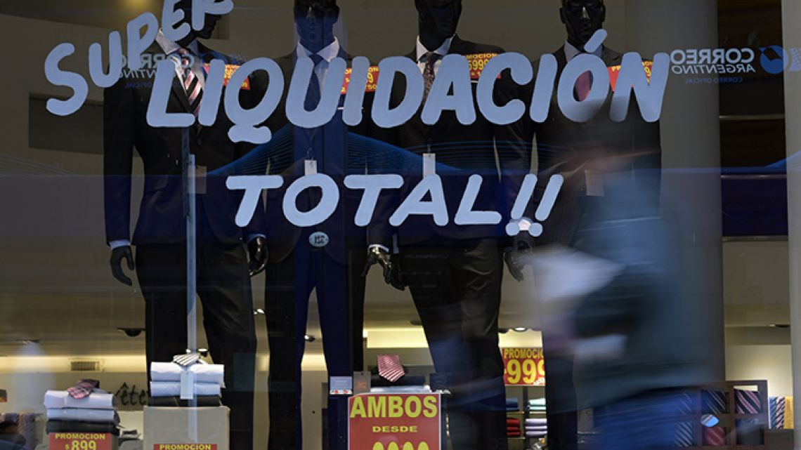 A man passes by a shop window with suits on sale in Buenos Aires.