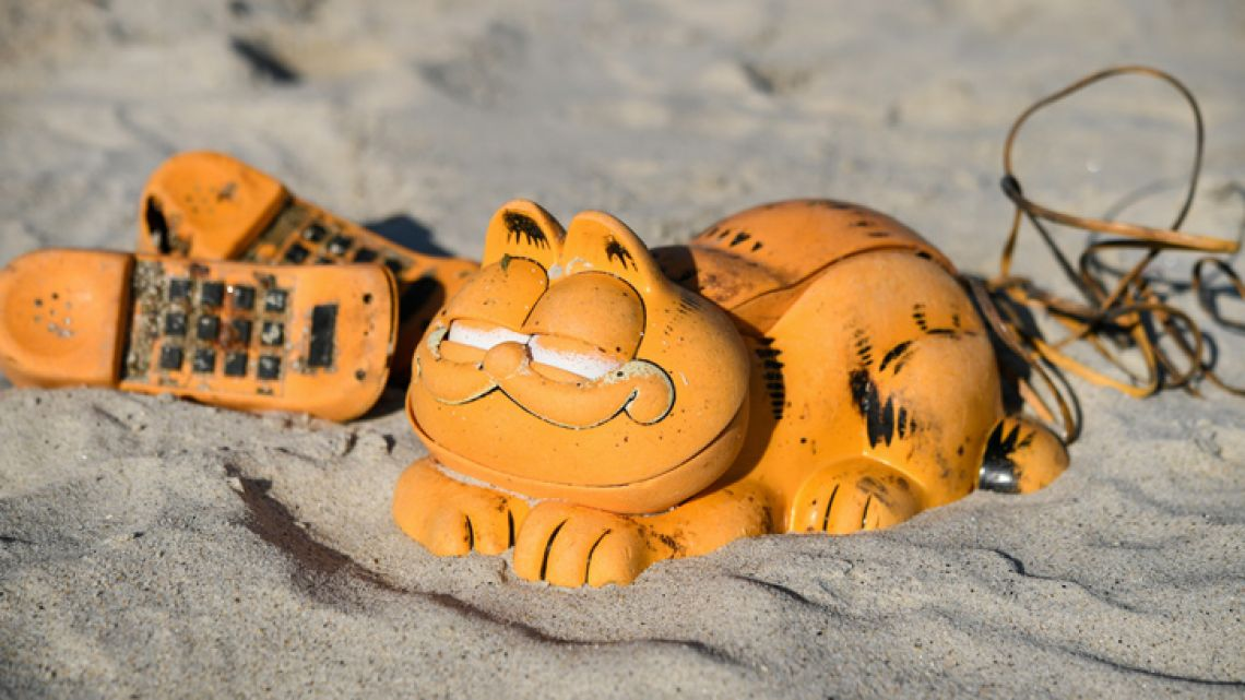 Spare parts of plastic 'Garfield' phones are displayed on the beach on March 28, 2019 in Plouarzel, western France, after being collected from a sea cave by environmental activists. For more than 30 years, plastic phones in the shape of the famous cat 'Garfield' have been washing up on French beaches. The mystery is now solved : a shipping container which washed up during a storm in the 1980s, was found in a hidden sea cave.