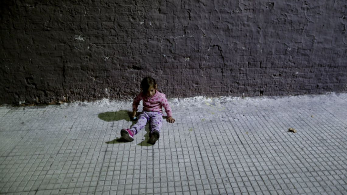 Valentina Aleman sits on the pavement. She lives on the streets with her family in Buenos Aires.