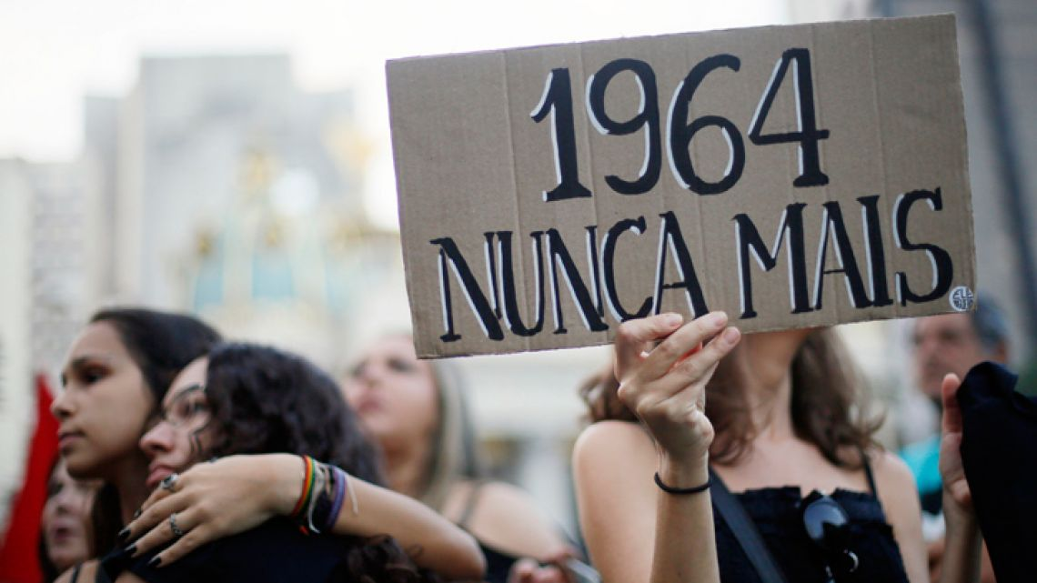 "A woman holds a sign reading ""1964 never again"", during a demonstration at Cinelandia square in Rio de Janeiro, Brazil on March 31, 2019, to protest against the commemoration of the 55th anniversary of the coup that established more than two decades of military rule."