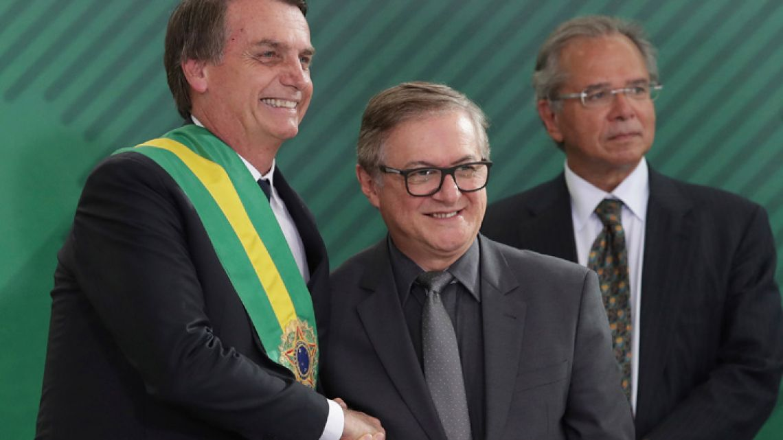 In this January 1, 2019 photo, Brazil's President Jair Bolsonaro, left, shakes hands with Education Minister Ricardo Vélez Rodríguez, during a swearing-in ceremony for his Cabinet at the Planalto presidential palace in Brasilia.