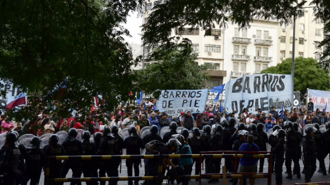 Demonstrators stand before a cordon of police on Av. 9 de Julio.