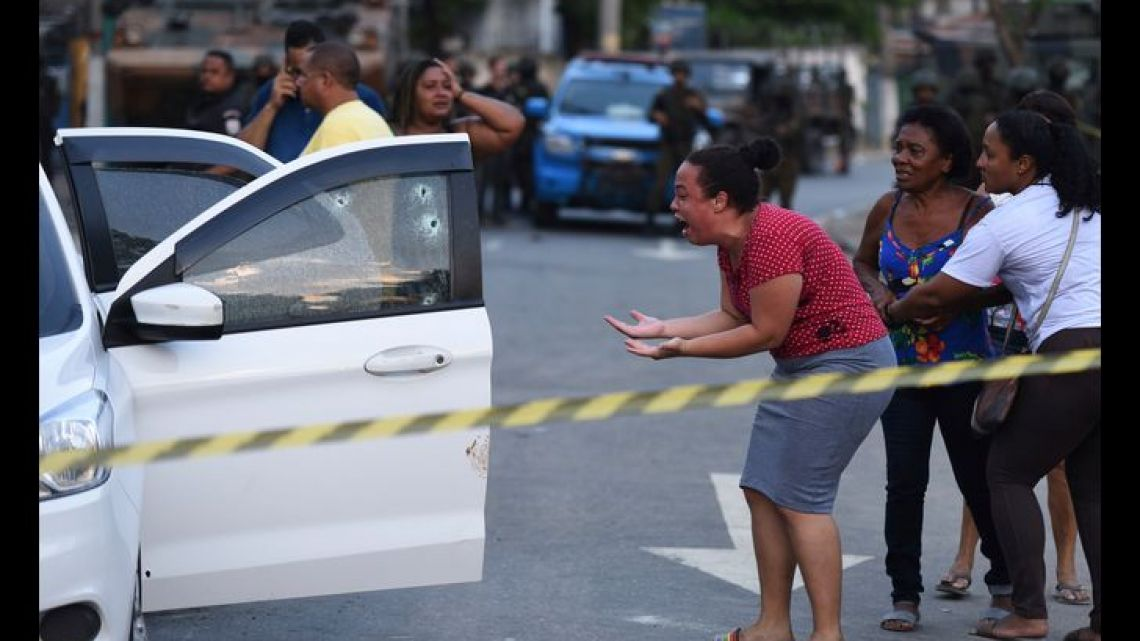 A relative of Evaldo dos Santos Rosa cries out as she sees his body slumped over inside his car in the Guadalupe neighborhood, Rio de Janeiro, Brazil, Sunday, April 7, 2019.