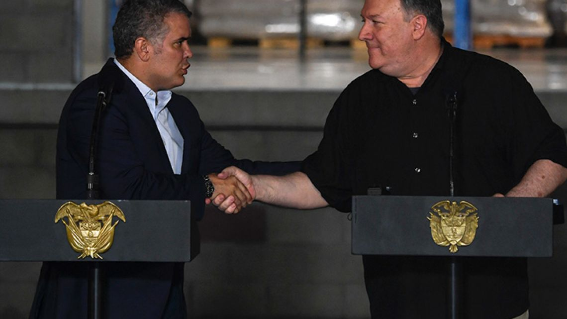 US Secretary of State Mike Pompeo (right) and Colombian President Iván Duque shake hands as they offer a statement to the press at the Tienditas International Bridge in Cúcuta, on the border with Venezuela, on April 14, 2019.