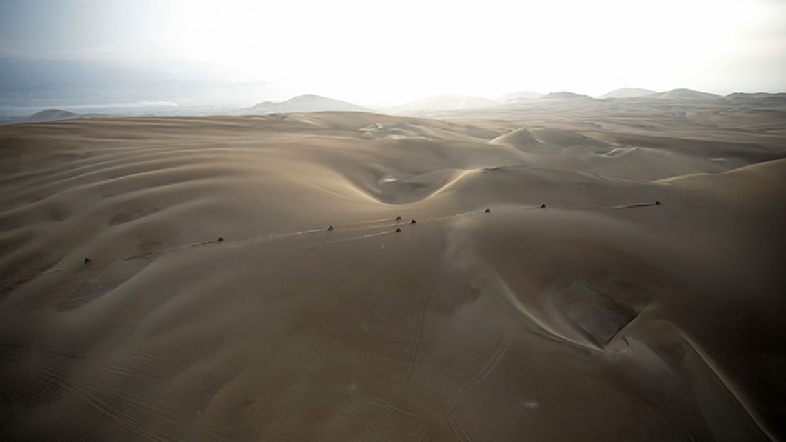 "Competitors ride their motorbikes across the dunes during stage nine of the Dakar Rally in Pisco, Peru. Dakar organisers say next year's cross-country race will be held in ""the deep and mysterious deserts of the Middle East, in Saudi Arabia."""