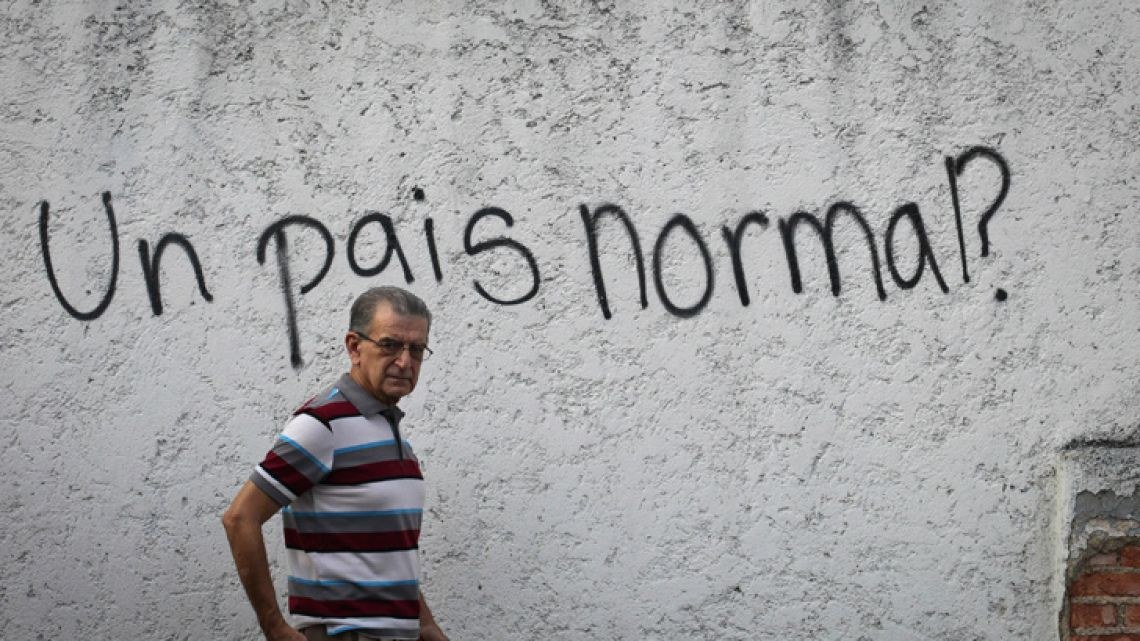 "Graffiti that reads ""A normal country?"" covers a wall in the neighbourhood of Alta Florida in Caracas."
