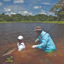 Pescador y guía asegurando la captura en el agua.