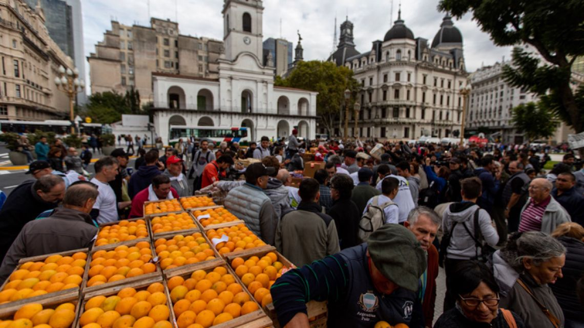 People line up to receive free fruit and vegetables, in front of the Casa Rosada.