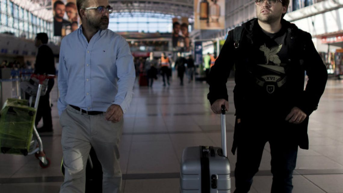 Tomás Ruiz pushes his suitcase as he is accompanied by his father Pablo at Ezeiza International Airport, before boarding a plane to Ireland.