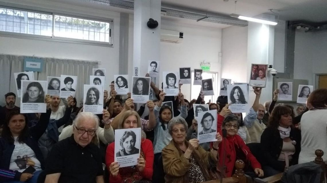 Victims and relatives of disappeared former detainees hold signs with the faces of their loved ones.