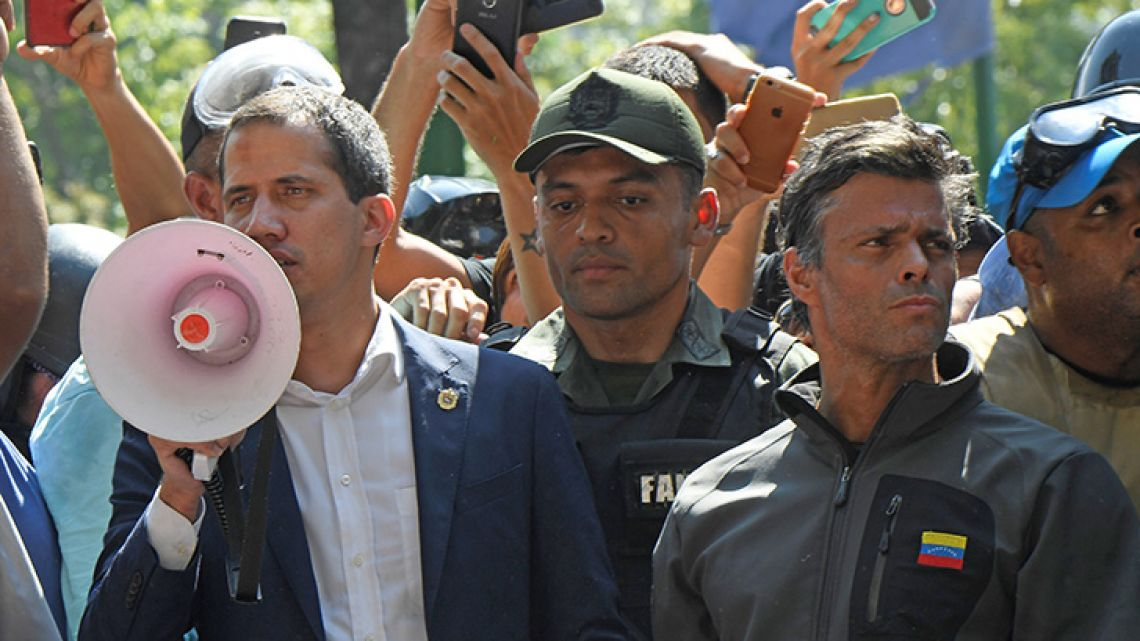 Venezuelan opposition leader and self-proclaimed acting president Juan Guaidó (left) speaks to supporters next to high-profile opposition politician Leopoldo López (right), who had been put under home arrest by Venezuelan President Nicolás Maduro's regime, and members of the Bolivarian National Guard who joined his campaign to oust Maduro, in Caracas on April 30, 2019.