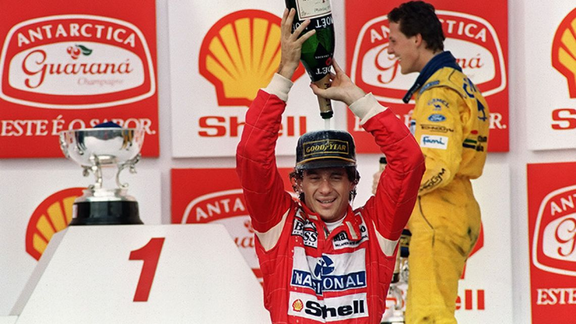 In this file picture taken on March 28, 1993, Brazilian Formula One driver Ayrton Senna pours champagne over himself celebrating his victory in the Brazilian Grand Prix in São Paulo, as German driver Michael Schumacher stands behind.