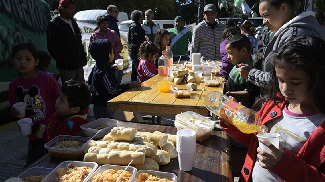 "Kids eat the stew prepared on the soup kitchen during the May Day meeting in Buenos Aires on May 1, 2019. Truckers Union commemorate May Day with a hundred of ""Ollas populares"" (soup kitchen) at the ""Canto al trabajo"" monument."