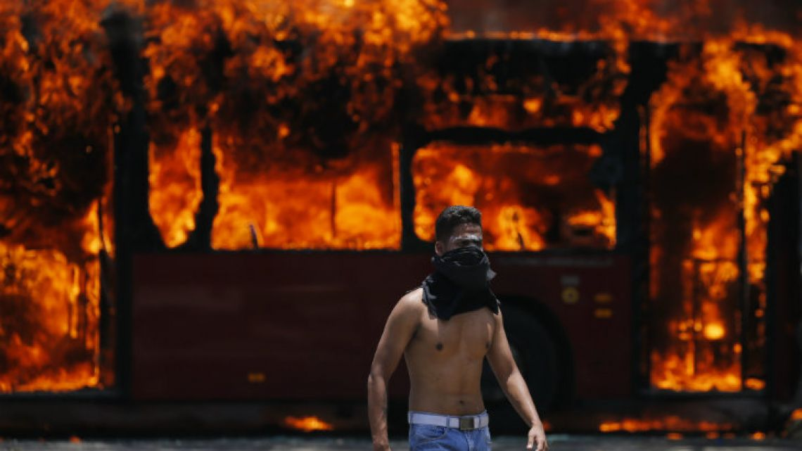 An anti-government protester walks near a bus that was set on fire in Caracas on Tuesday.
