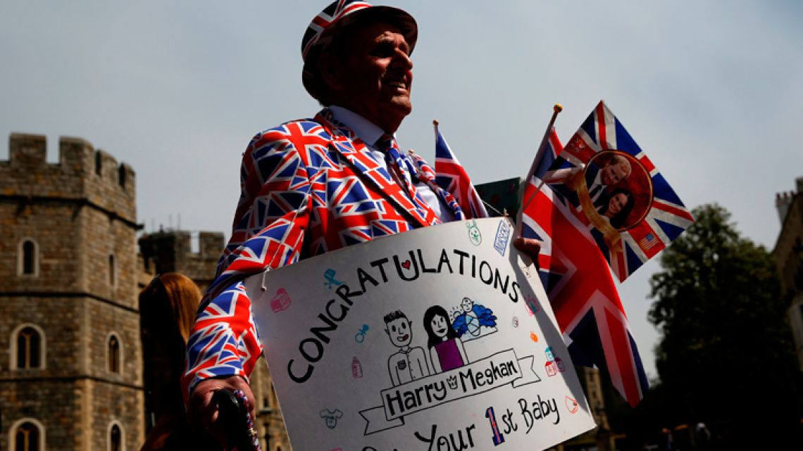 Royal super fan Terry Hutt, wearing a Union-flag themed suit, holds a congratulatory banner as he walks outside Windsor Castle.