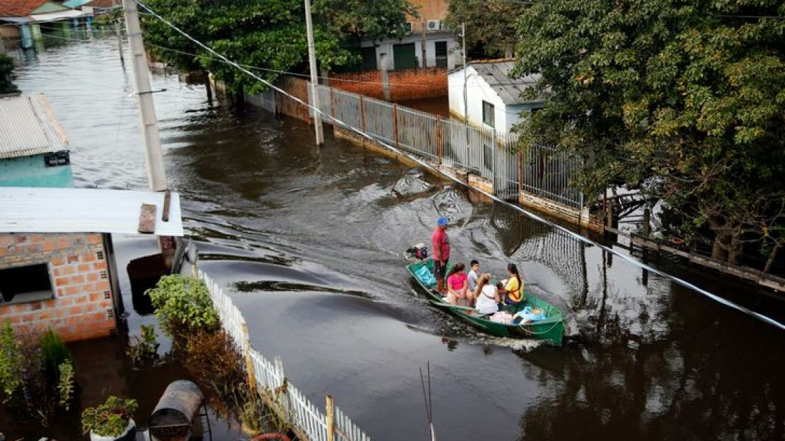 A boat transports people in Asuncion, Paraguay, who have been displaced by a flooded street on Wednesday, May 8, 2019.