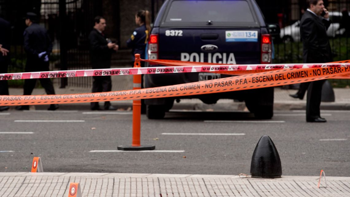 Police stand near the crime scene where lawmaker Héctor Olivares was seriously injured and another man killed after they were shot at from a parked car near the National Congress building, in Buenos Aires, Argentina, Thursday, May 9, 2019.