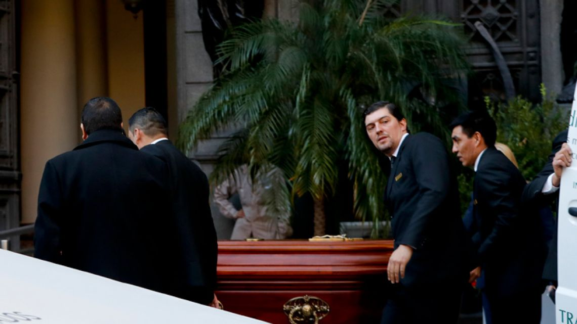 Funeral service employees enter Congress carrying the coffin of late lawmaker Héctor Olivares for a wake in Buenos Aires on Monday, May 13, 2019.