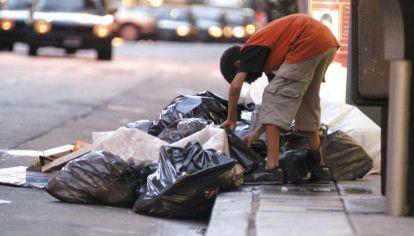 Un chico revolviendo la basura. Postal de la pobreza.
