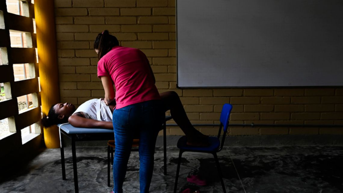 Colombian medical doctor of the San Raffaele hospital ship, Durley Maya, checks a pregnant woman at a classroom improvised as office in Isla Mono, in the San Juan river, Choco department, Colombia, on April 23, 2019. In Isla Mono, located in the coastal municipality of San Juan, they haven't had the presence of doctors for years, there is neither electricity nor potable water. Midwives there have been fundamental for the birth of its inhabitants.
