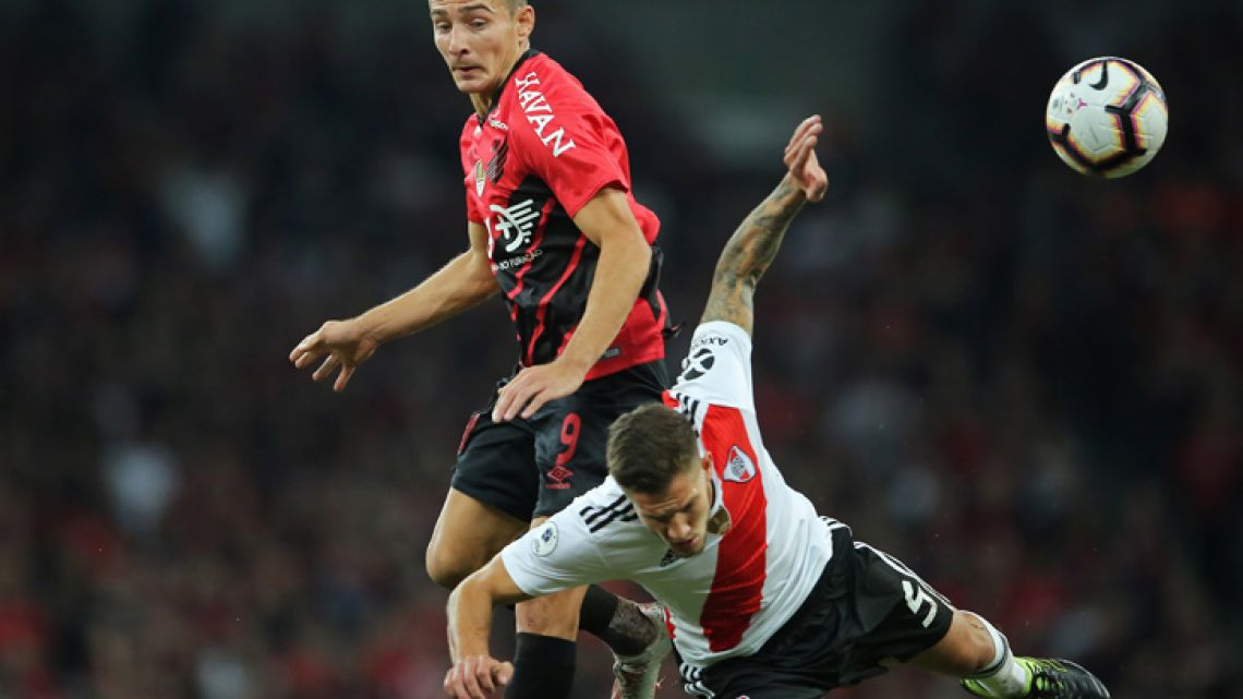 Marco Ruben (top) of Brazil's Athletico Paranaense struggles for the ball with Bruno Zuculini (bottom) of Argentinas's River Plate during a Recopa Sudamericana 2019 first leg football match at the Arena da Baixada stadium, in Curitiba, Brazil, on May 22, 2019.