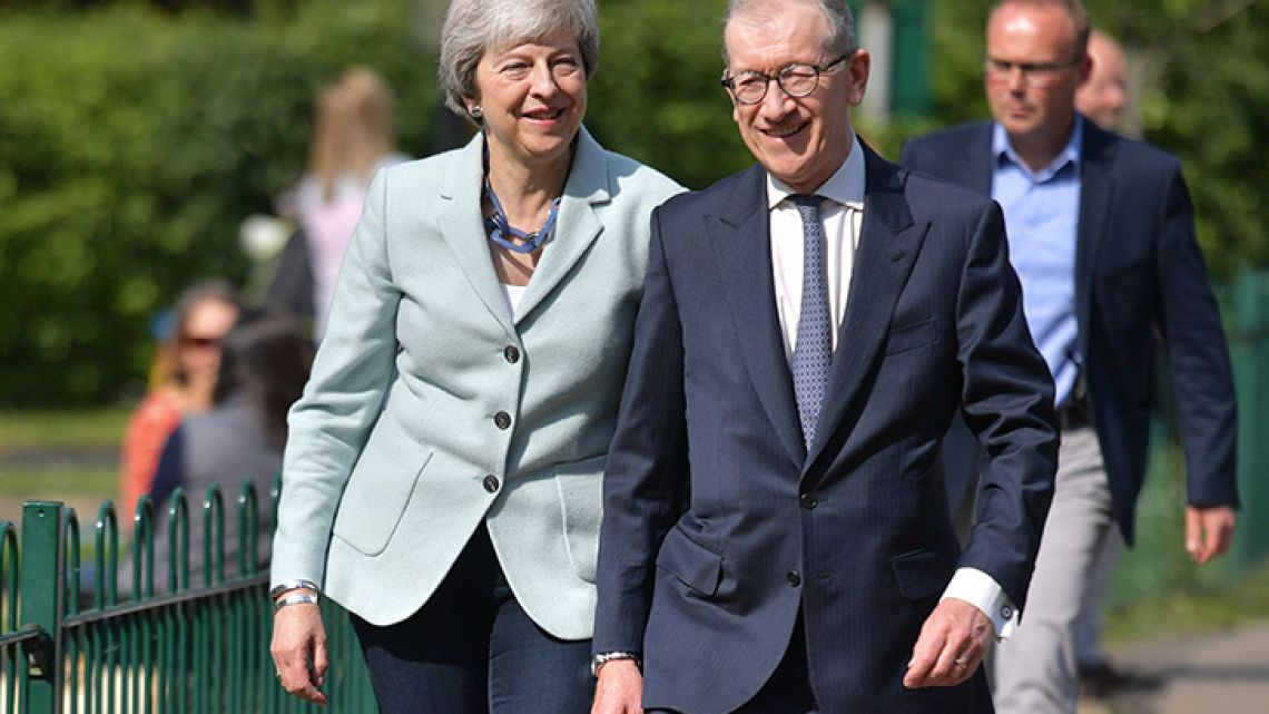 Britain's Prime Minister Theresa May (left) and her husband Philip May (right) arrive to vote in the European Parliament elections in Sonning, west of London, on May 23, 2019.