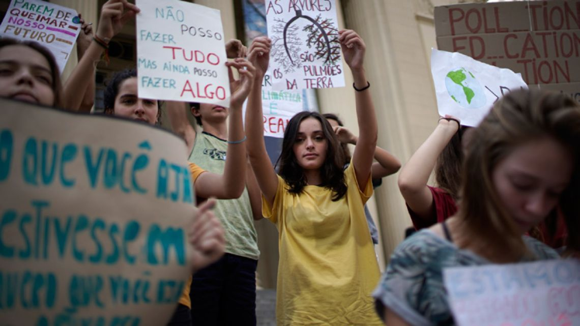 Students protest President Jair Bolsonaro's environmental policies in front the state legislature in Rio de Janeiro, Brazil, Friday, May 24, 2019. A small group of students gathered outside the state legislature to deliver a letter dated from the future in which they lamented Brazil's loss of coastline, rainforests and species.