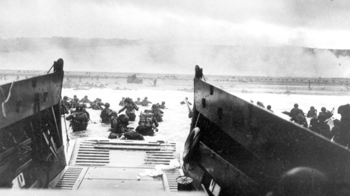 In this June 8, 1944, file photo, under heavy German machine gun fire, US infantrymen wade ashore off the ramp of a Coast Guard landing craft during the invasion of the French coast of Normandy in World War II. June 6, 2019, marks the 75th anniversary of D-Day, the assault that began the liberation of France and Europe from German occupation, leading to the end World War II.