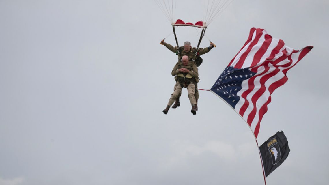 US World War II D-Day veteran Tom Rice parachutes in a tandem jump into a field in Carentan, Normandy, France, Wednesday, June 5, 2019. Approximately 200 parachutists participated in the jump over Normandy on Wednesday, replicating a jump made by US soldiers on June 6, 1944 as a prelude to the seaborne invasions on D-Day.