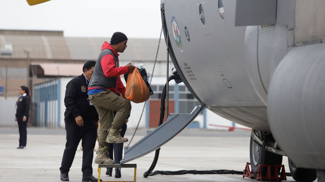 In this photo provided by Peru's presidential press office, a Venezuelan immigrant enters an airplane to be deported home, along with other Venezuelans, at a military base in Callao.
