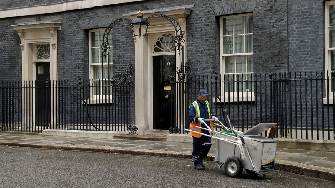 A street cleaner empties a rubbish bin in Downing Street, London, Friday, June 7, 2019. Prime Minister Theresa May is stepping down as Britain's Conservative party leader later Friday, defeated by her failure to take Britain out of the European Union on schedule. She will remain as prime minister for a few weeks while the party picks a successor.
