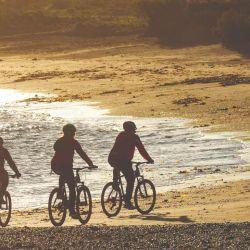 Pedalear en MTB por la playa El Arroyo permite disfrutar el atardecer junto al mar.