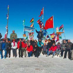Los miembros de la travesía posan en la plaza de las banderas, en el ingreso del salar.