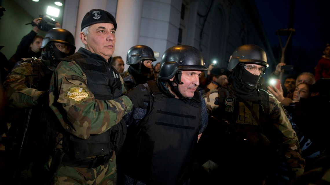 In this June 14, 2016 file photo, former Public Works Secretary Jose Lopez, center, is escortED by police outside the a police station in the outskirts of Buenos Aires, Argentina.