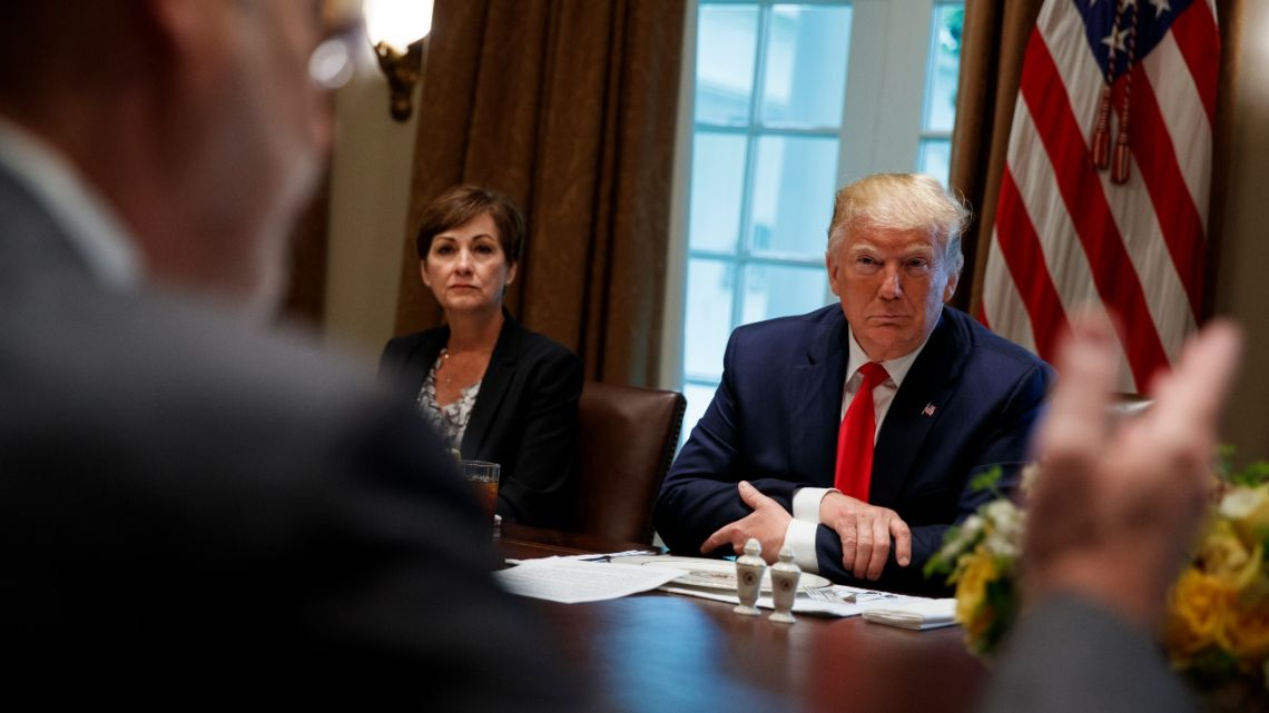 "Iowa Gov. Kim Reynolds and President Donald Trump listen as Pennsylvania Gov. Tom Wolf speaks during a meeting with governors on ""workforce freedom and mobility"" in the Cabinet Room of the White House, Thursday, June 13, 2019, in Washington."