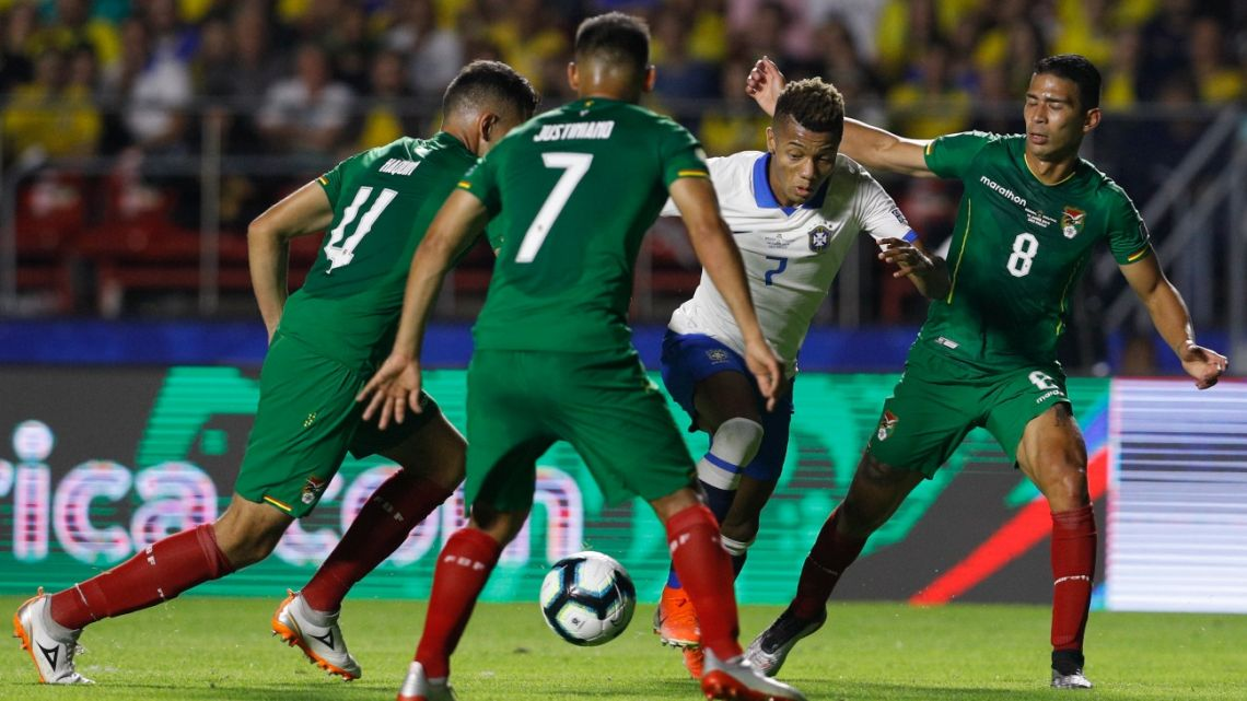 Brazil's David Neres is surrounded by Bolivia's Luis Haquin, left, Leonel Justiniano (7) and Diego Bejarano during a Copa America Group A soccer match.