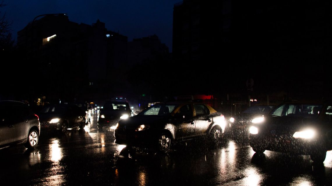 In this June 16, 2019 file photo, cars drive through an unlit street during a black-out in Buenos Aires.