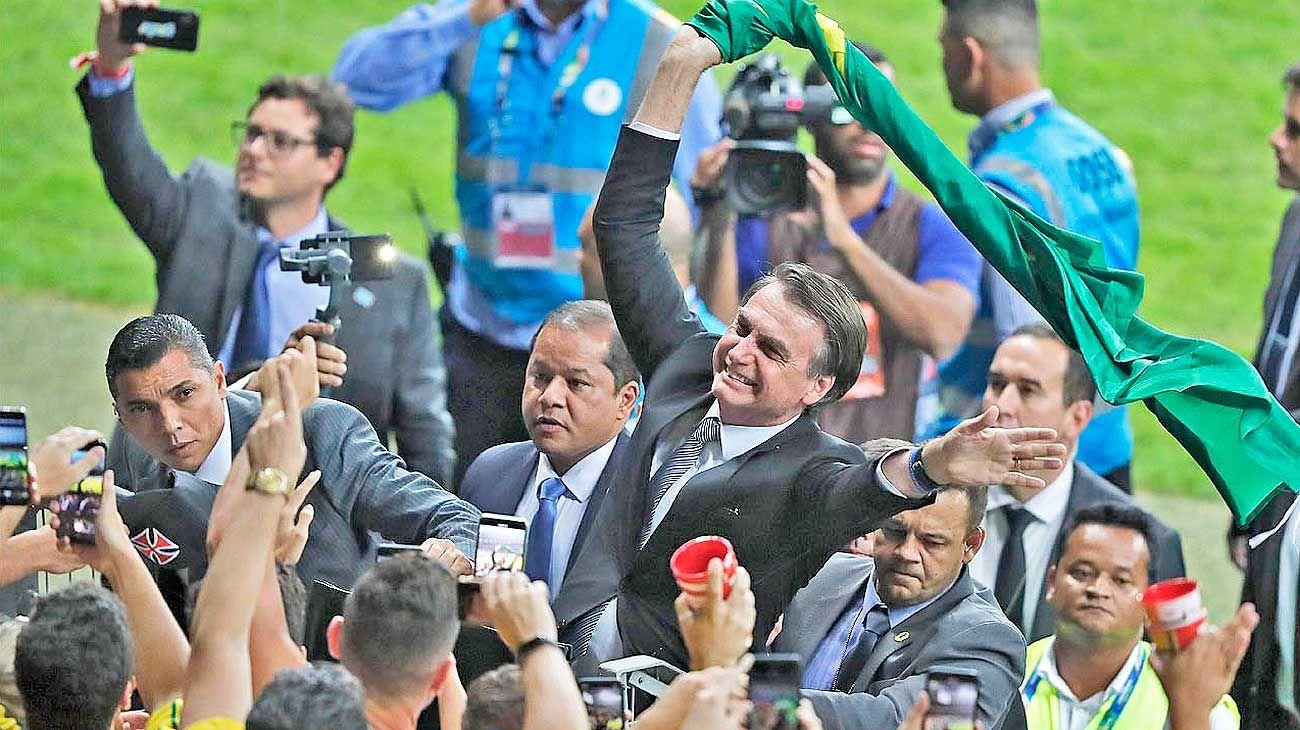 """Que de la mano. El presidente brasileño hizo un show en el entretiempo de Brasil-Argentina, que incluyó minivuelta olímpica y bandera """"verdeamarelha""""."""