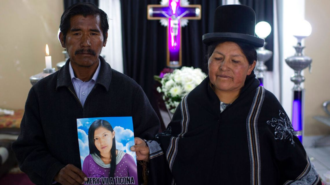 "Celso Vila and Luisa Ticona pose with a photo of their late daughter Mery Vila inside the ""Stairway to Heaven"" funeral home, in La Paz, Bolivia, Thursday, July 11, 2019. Vila's partner killed the 26-year-old woman by striking her several times on the head with a hammer."